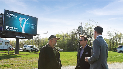 Customers speak with Watchfire territory managers at the base of a billboard structure.